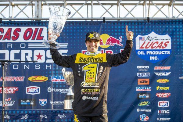Zach Osborne holding trophy on podium